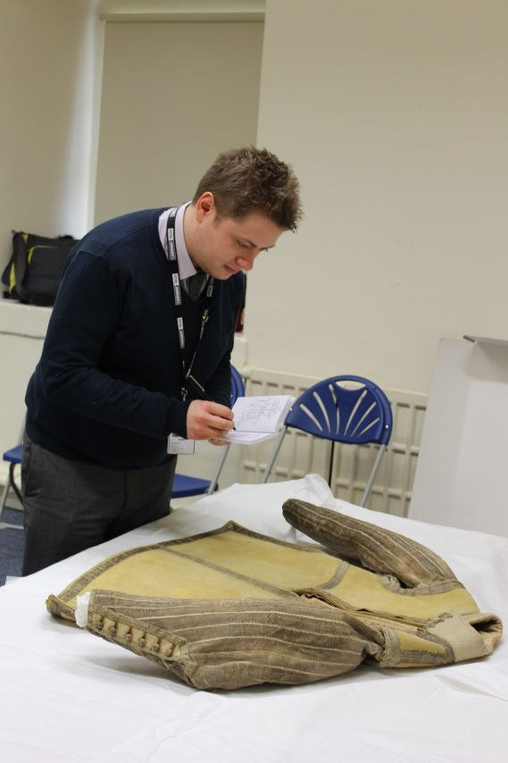 Curator examines the buff leather coat
