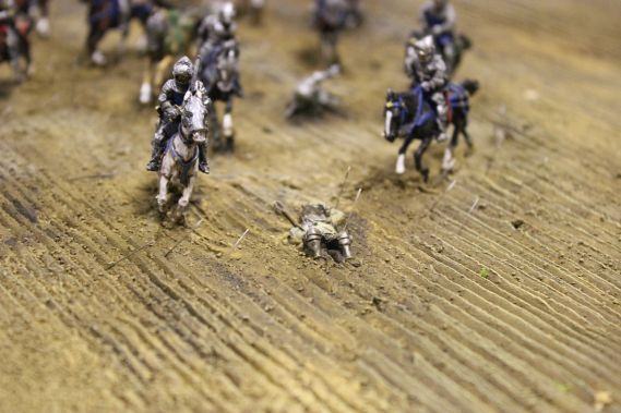 miniature model of a soldier lying on the floor and cavalry charging