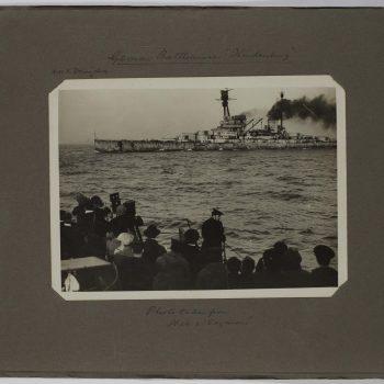 crowd watching battleship at sea