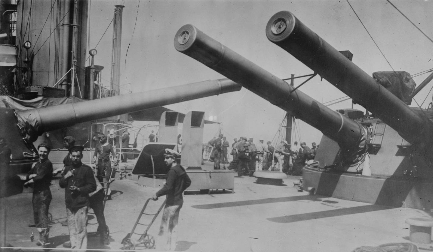 Crew onboard a First World War battleship in front of its large guns