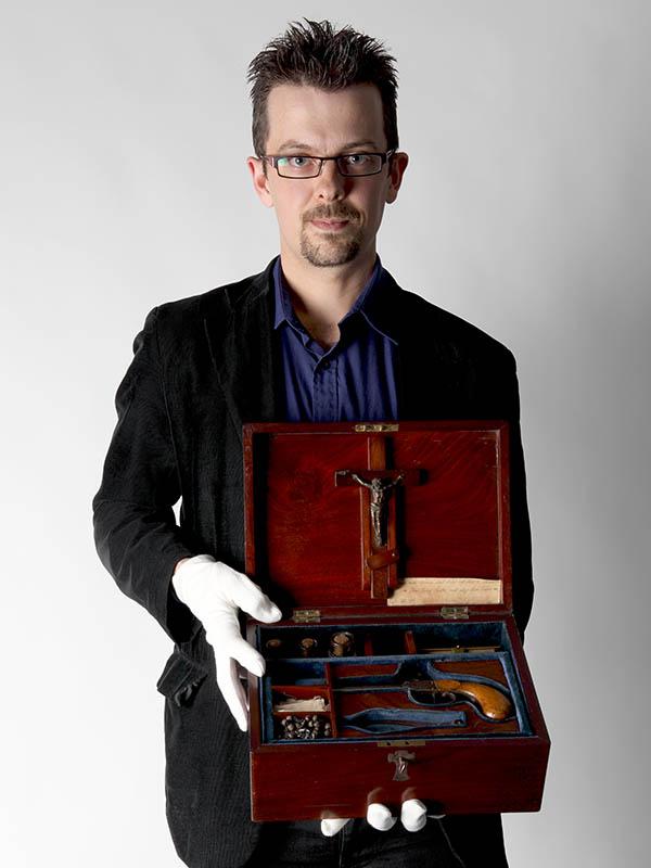 Man wearing glasses holds the vampire killing kit