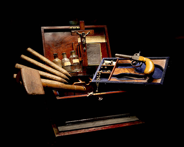 An open mahogany case dispalying all the elements of a vampire killing kit