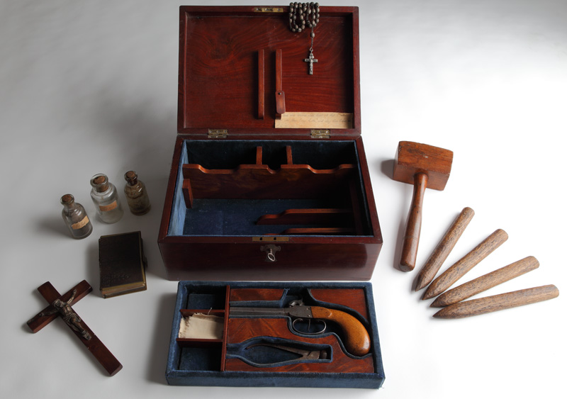 Box for the kit with it laid out around it, including stakes and mallet, cross, prayer book, gun and holy water