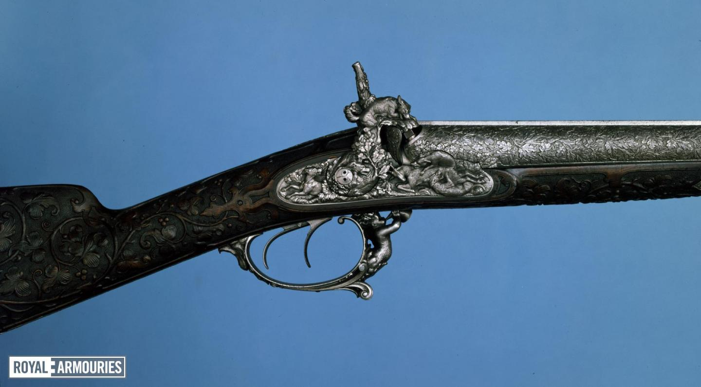 Flintlock gun showing a decorated lock plate and trigger guard