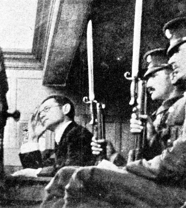 Hans Lody sitting in the dock guarded by two armed soldiers