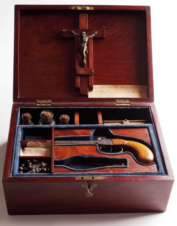 mahogany case with a pistol, bullets and a crucifix on the lid