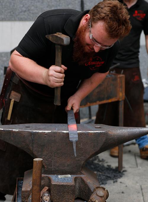 man hammering red hot sword blade