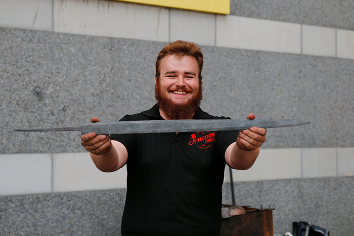 A happy blacksmith presents the finished sword blade