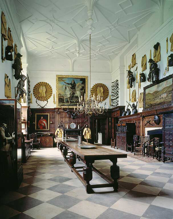 A room with with hanging paintings and armour adorning the walls