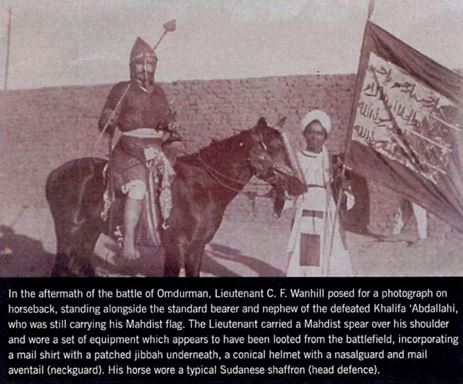 photograph of man on horseback in chain mail armour next to a young man holding a flag