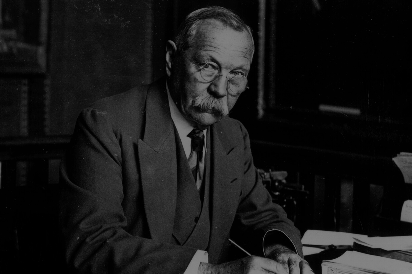 Older gentleman with glasses and moustache sitting at desk covered in papers, pen in hand.