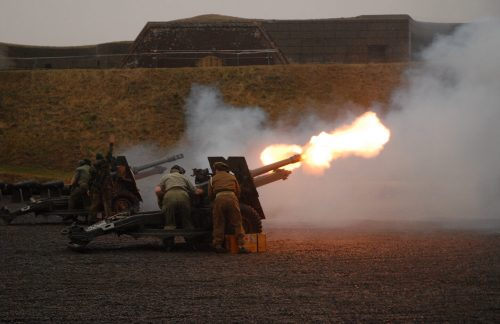 a 25-pounder gun firing and spewing flames from the muzzle