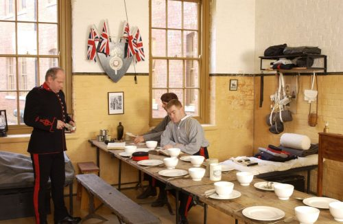 Soldiers sit in a World War 1 kitchen and dining room with a table set for 8