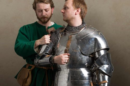 A squire dresses his knight in armour