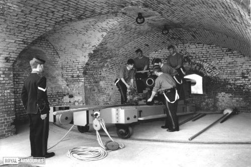 6 men in Victorian uniform loading a large gun in a brick alcove