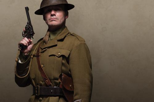 Man in khaki uniform and tin helmet holding a pistol