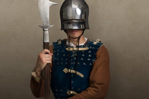 medieval soldier in helmet and carrying a bill hook