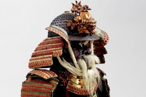Japanese samurai orange and gold armour with a helmet crowned with a crouching lion and face mask with a white beard