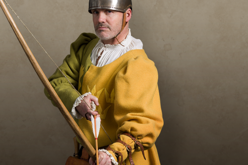 Medieval bowman in yellow tunic preparing to shoot