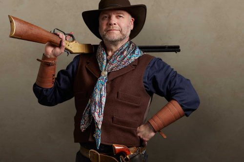 A smiling cowboy stands with rifle over shoulder and hand on hip