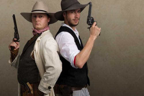 Gun toting men stand back to back preparing to duel at High Noon