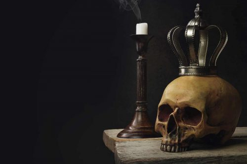 A silver crown sits atop a yellowed skull beside an extinguished smoking candle