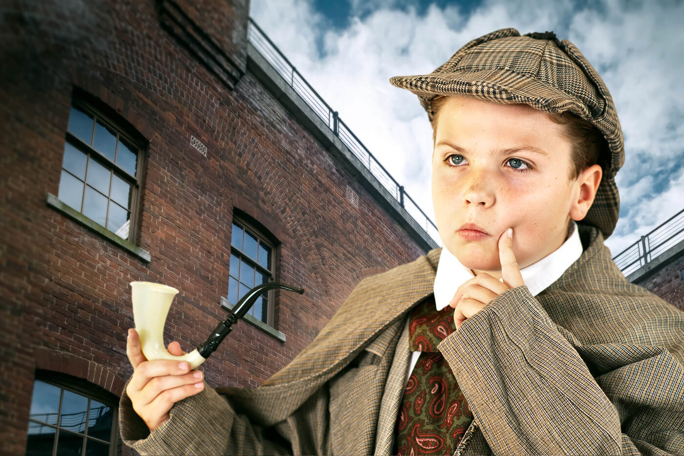 A child dressed as sherlock holmes with the Fort in the background