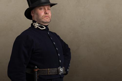 Man in Victorian style dark blue uniform with top hat