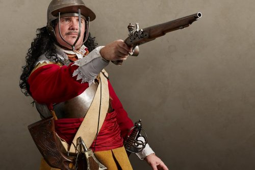 Royalist cavalier soldier dressed in a red tunic, buff coat, breastplate and a three-bar helmet, pointing a flintlock pistol
