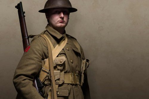 First World War British soldier in battle dress, tin hat and rifle over shouder