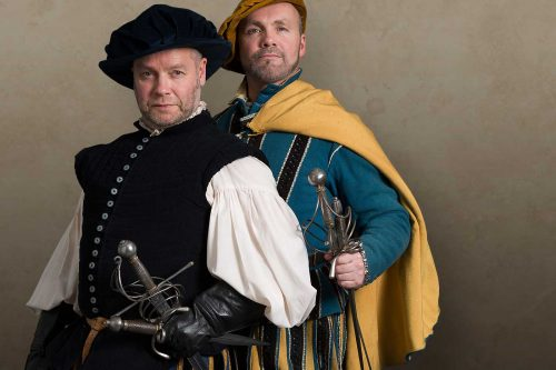Two flamboyantly dressed Renaissance sword masters posing with their swords