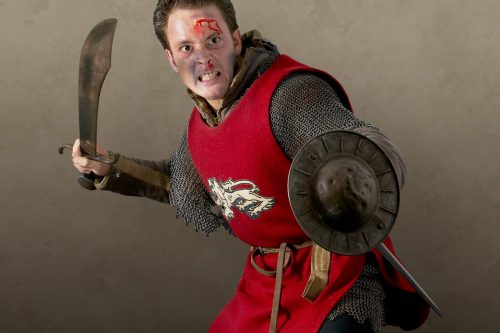 medieval warrior in mail and red tabard weilidng a sword and buckler