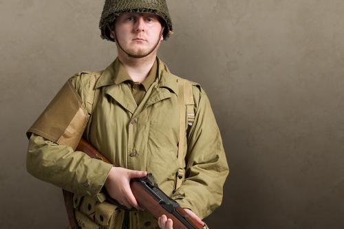 Man in khaki uniform and tin helmet holding a rifle