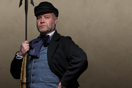 Man wearing black jacket and blue waistcoat and holding a harpoon.