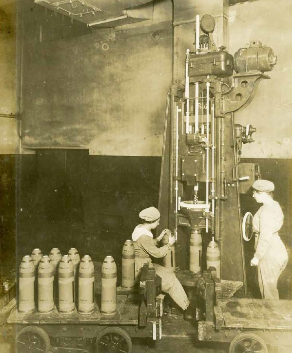 Sepia archive photograph of two women loading shells into an extruder machine