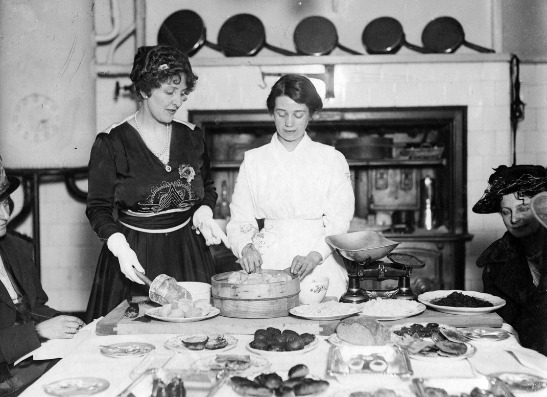Black and white archive photograph of two women stood behind a table laid with food.