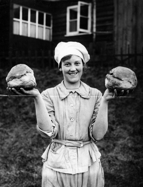 Black and white archive photograph of smiling women in white overalls holding a loaf of bread up in each hand