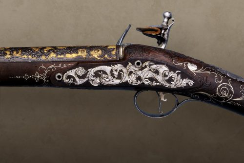 Side view of flintlock musket decorated with gold and silver inlaid foliage