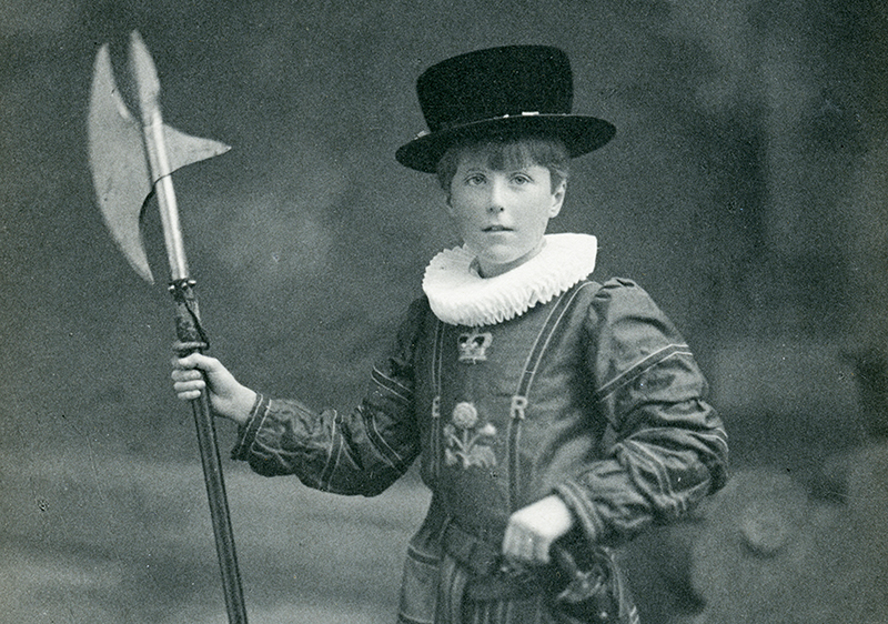 Black and white photogrpah of a young boy dressed as a yeoman warder - wearing a white ruff, black hat and carrying a staff weapon