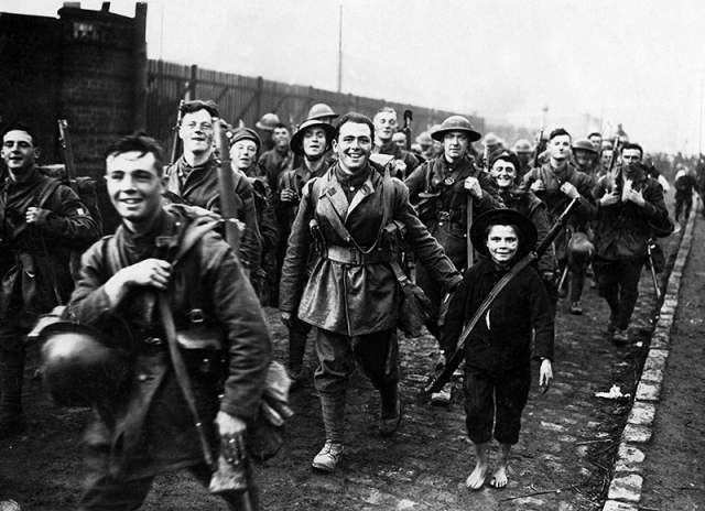 Black and white photograph of marching smiling men from the first world war with a child carrying a rifle