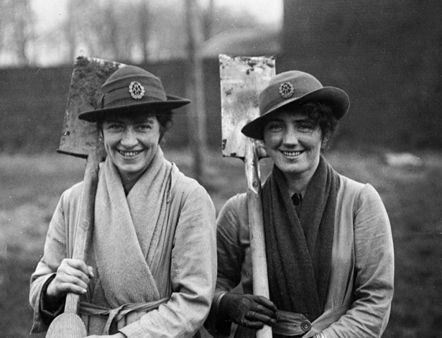 Black and white photograph showing two smiling women in uniform holding spades over their shoulders