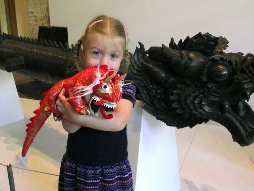Young girl holding red toy dragon