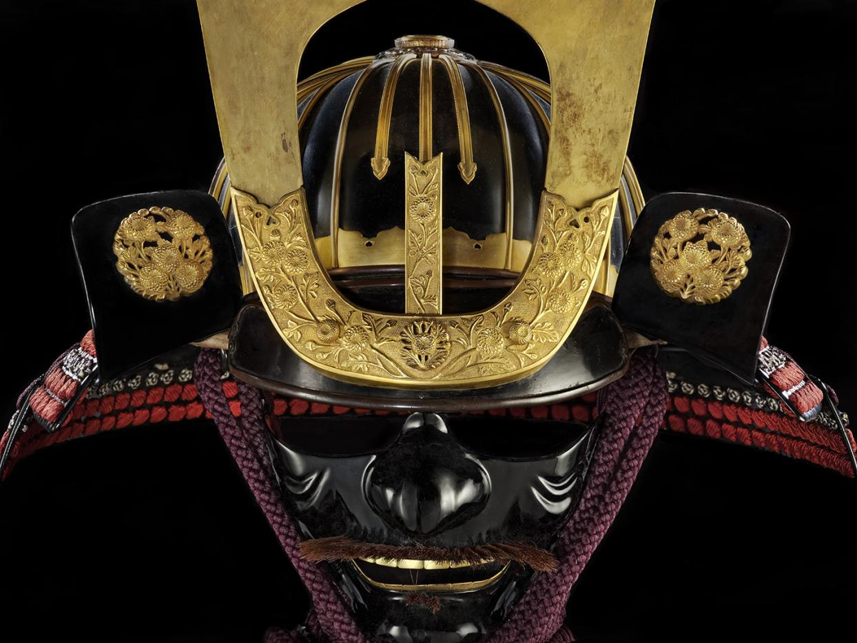 shiny black and gold Japanese mask and helmet with red lacing