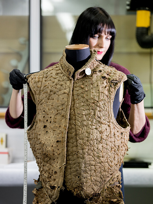a conservator stood behind a brown fabric jacket measuring it