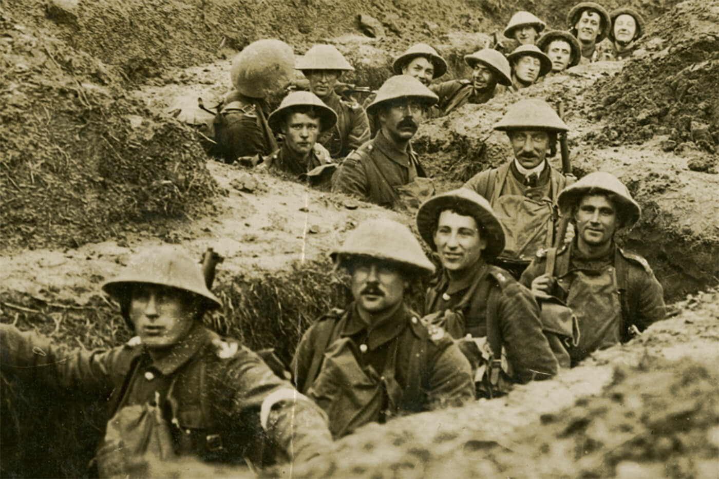 Black and white archive image of men stood in line in trenches