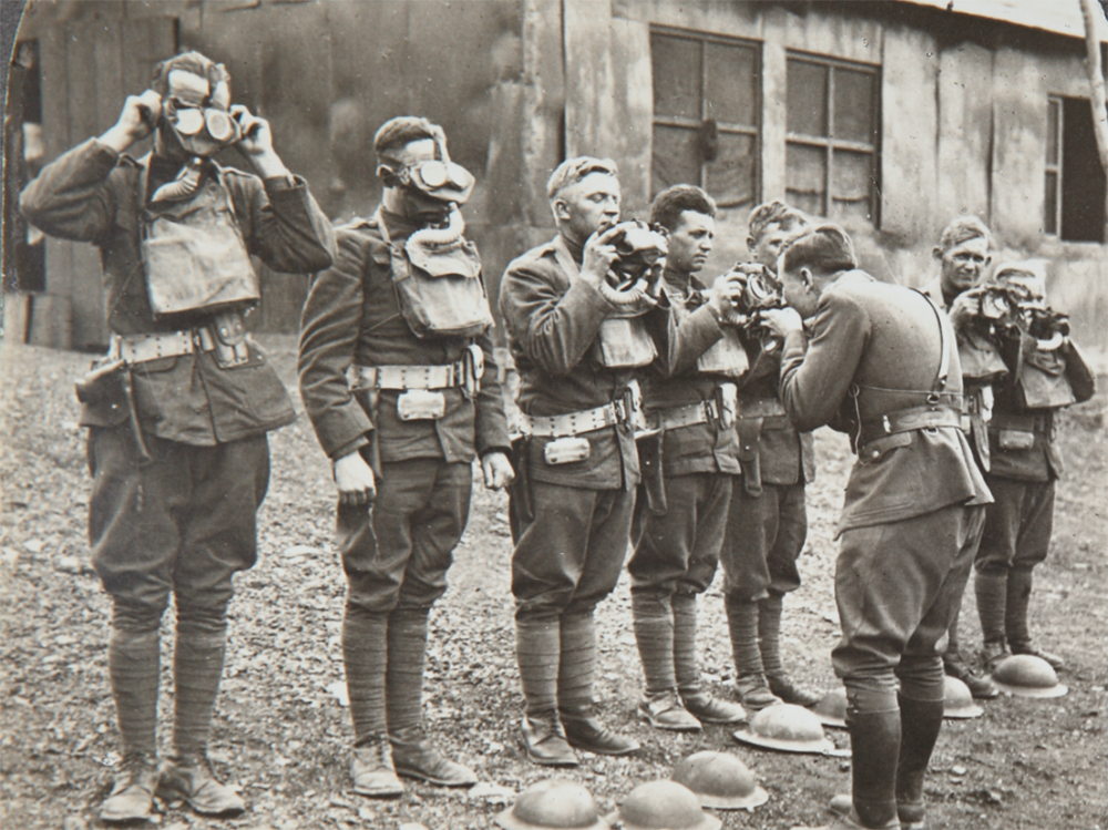 Black and white archive footage of men stood in a line trying on gas masks