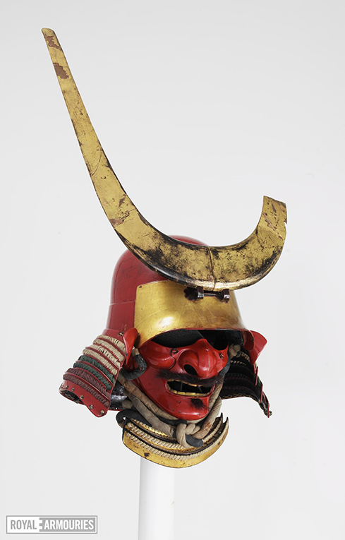 The mask in full, showing the gold lacquered crest which sits on the front of the helmet