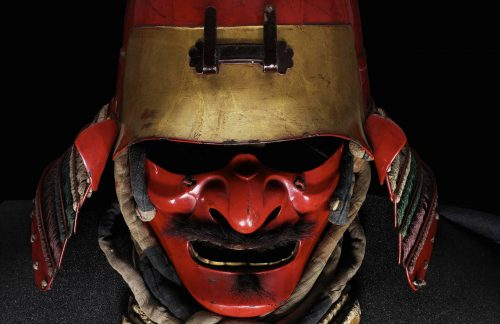 Red and gold japanese helmet and face mask with a moustache.