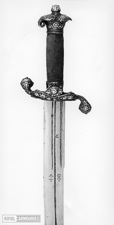 Close up of the cross guard of a Hangar, with dotted pattern on cross guard and pommel and velvet grip