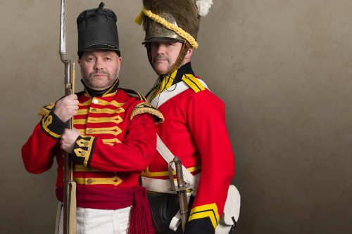 A cavalry officer and a redcoat infantryman posing in their uniforms